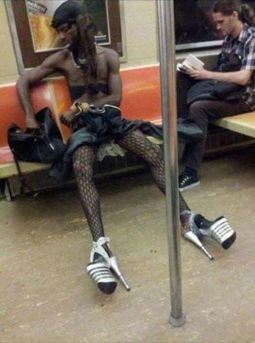 Hombre en el metro con mallas de red y tacones altísimos