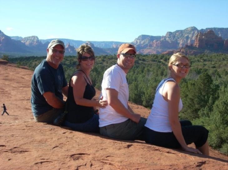 Foto de una familia, al fondo se ve una persona muy chiquita