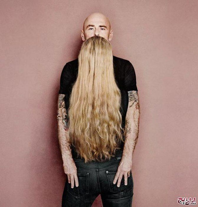 Fotografía en donde parece que un hombre tiene una barba larga pero realmente está abrazando a una mujer con el cabello largo