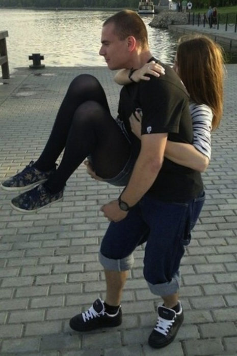 Hombre cargando a mujer de lado pero da la impresión que es ella quien carga a él