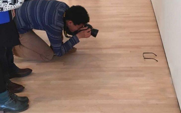 Turista toma fotografías de unos lentes tirados en un museo