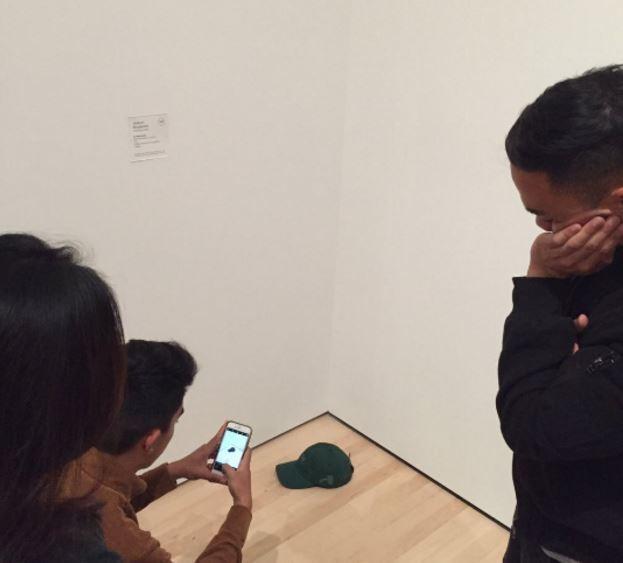 Personas toman fotografías de una cachucha en un museo