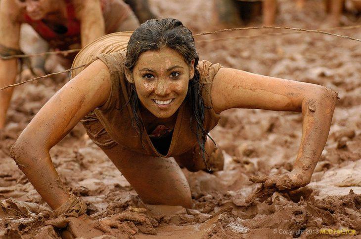 Una mujer en una competencia está llena de lodo pero sale guapa en la foto