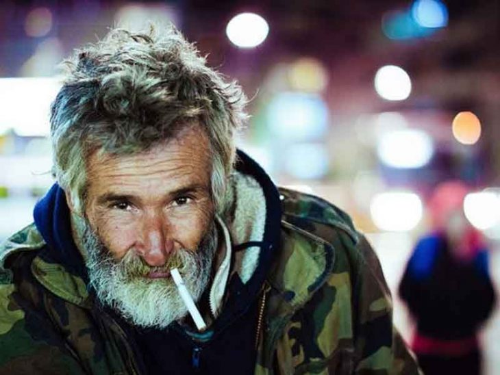 Un vagabundo mira a la cámara mientras se fuma un cigarro