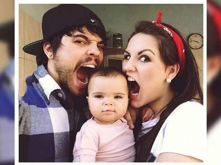 Unos papás se toman una foto con su niña mientras la niña sale perfectametne calmada y hermosa