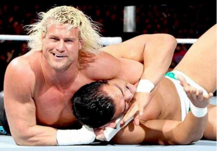 Un luchador derriba a su oponente mientras sonríe para la cámara