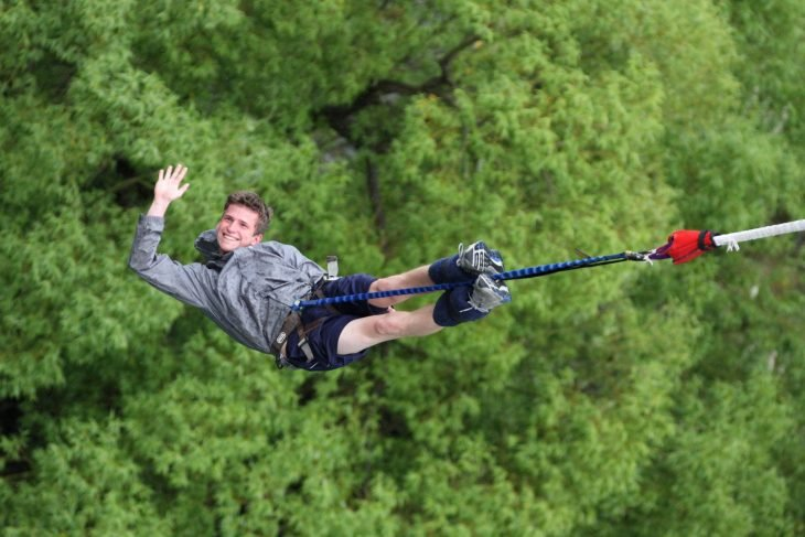 Un joven salta del bungee con una sonrisa y aspecto relajado