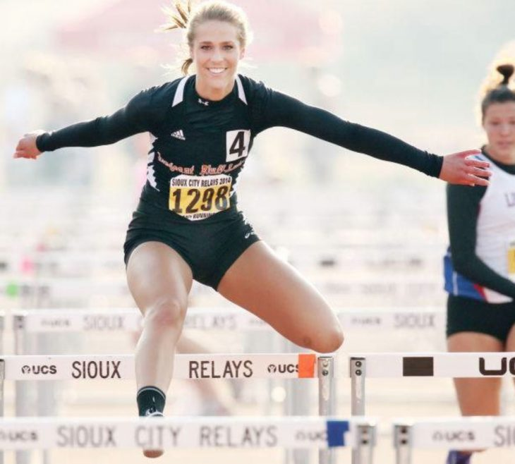 Una mujer saltando obstáculos en una carre que parece que está posando para la foto