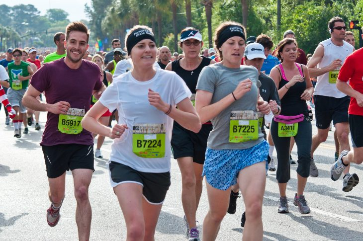 Fotografía de atletas en un maratón, un joven sonríe a la cámara y sale ridículamente guapo