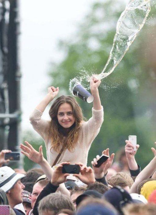 Una mujer en un concierto sonríe para la cámara antes de que un vaso con una bebida la golpee en la cabeza