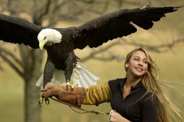 Una mujer le toman una fotografía mientras un águila real está en su muñeca