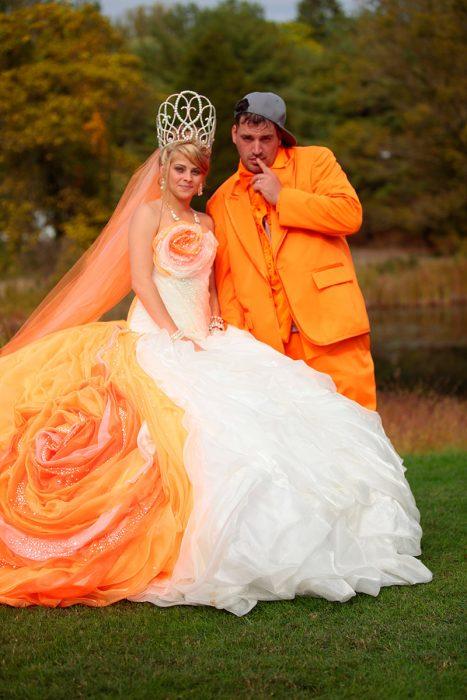 Novia con el velo naranja, corona de reina y en su vestido tiene cosas naranjas simulando una flor. El novio va vestido todo de naranja con una gorra gris de lado