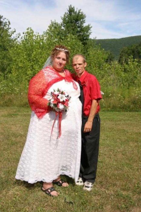 Novia usando un vestido de novia con un chal rojo arriba y sandalias negras