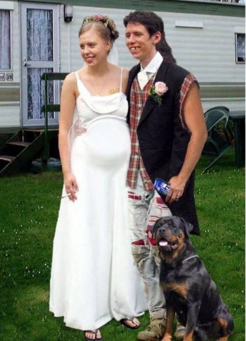 Foto de novios. La novia está embarazada, con sandalias y un cigarro, el novio con pantalones rotos, chimuelo y una cerveza. Atrás se ve una casa remolque y en la foto aparece un perro