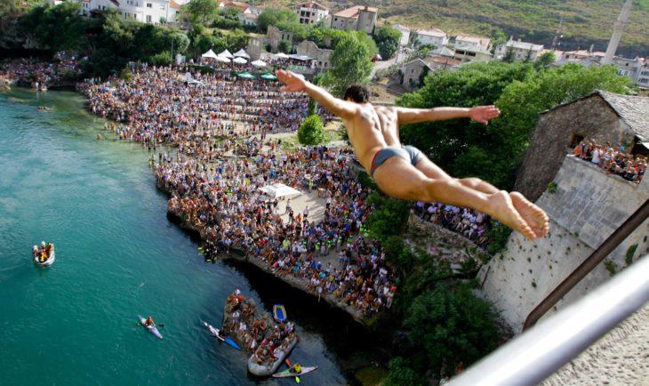Hombre aventándose del Puente Viejo en Bosnia, clavadista