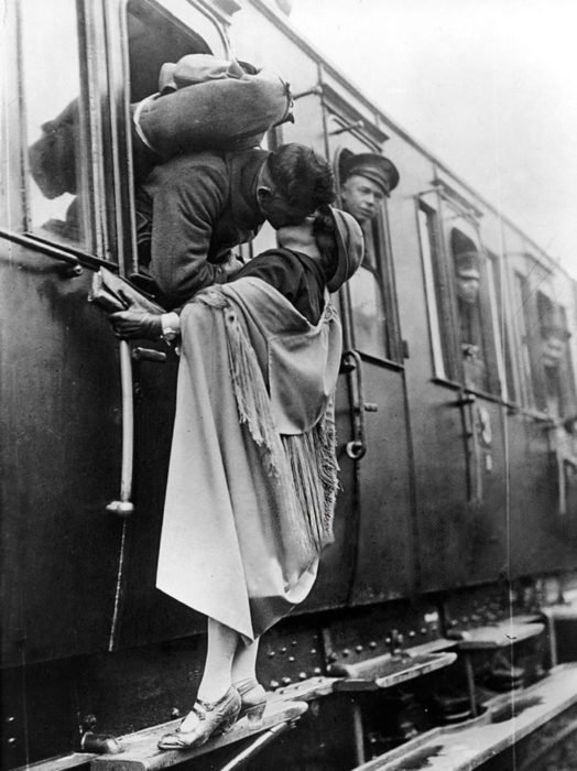 Amor en tiempos de guerra. soldado sale de la ventanilla del tren para besaar a una mujer que está en el escalón de la parte de afuera del tren