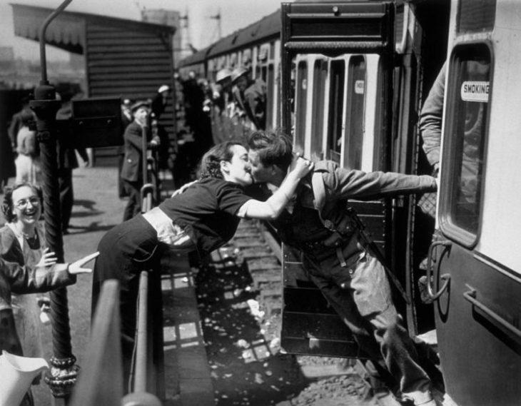 Amor en tiempos de guerra. mujer brinca la cerca para besar a un soldado que sale del tren