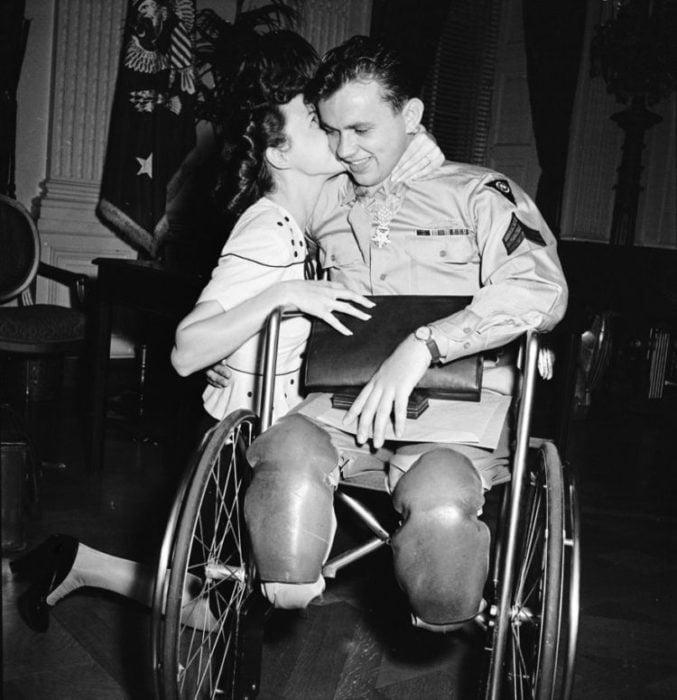 Amor en tiempos de guerra. soldado con las piernas amputadas y mujer arrodillada besándolo