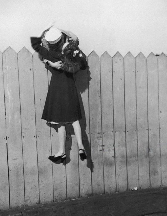 Amor en tiempos de guerra. marinero carga a su novia y le besa del otro lado de la cerca