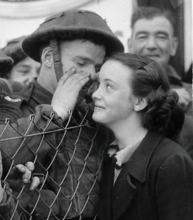 Amor en tiempos de guerra. un soldado le susurra algo a una mujer mientras ésta sonríe