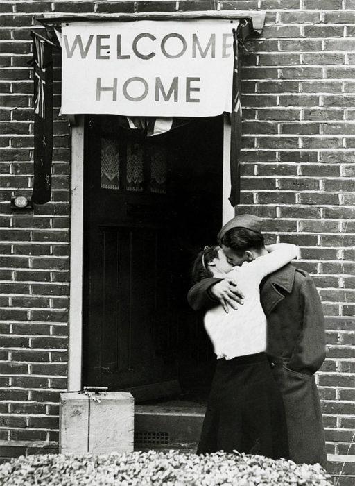 Amor en tiempos de guerra. soldado y mujer se besan en la puerta de una casa que tiene un letrero de welcome home
