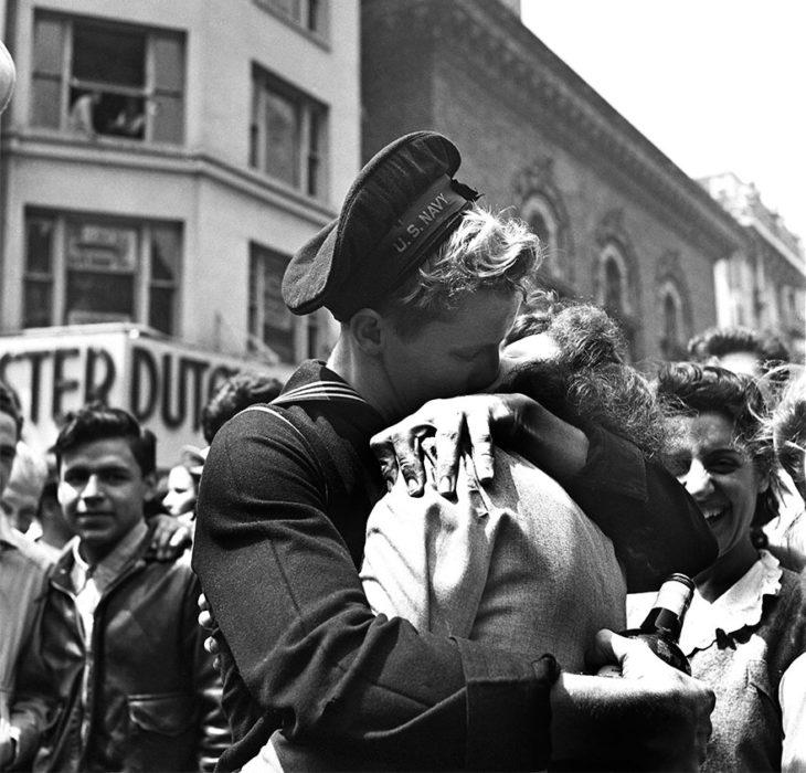 Amor en tiempos de guerra. soldado con una botella de vino abraza y besa a una mujer mientras otros ven