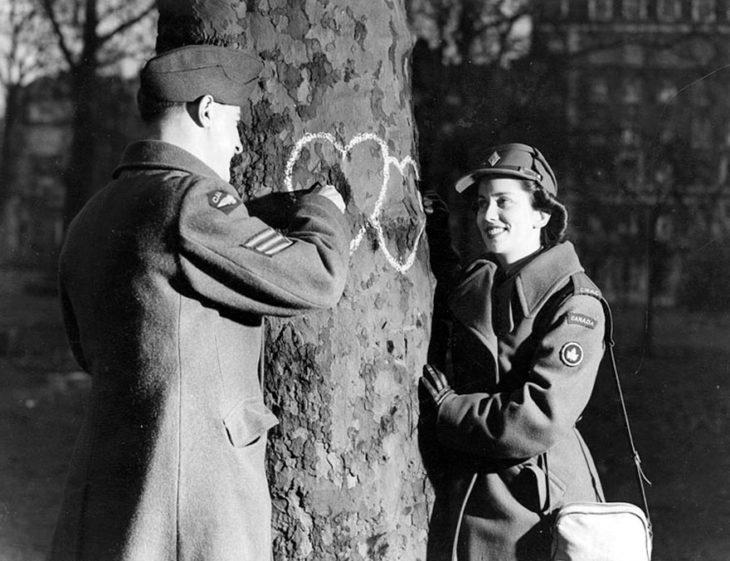Amor en tiempos de guerra. soldado y mujer marcan dos corazones en un arbol