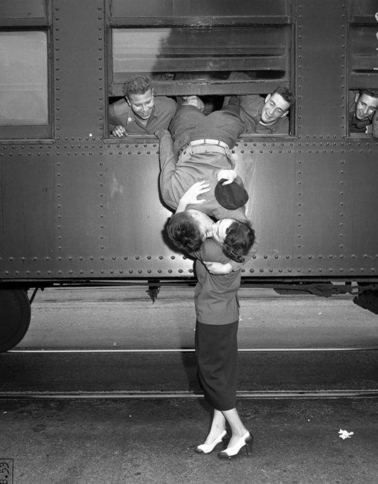 Amor en tiempos de guerra. dos soldados sostienen las piernas de otro que sale de la ventana de un camión para besar a la mujer que está abajo