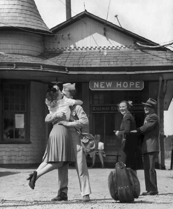 Amor en tiempos de guerra. mujer besando a un soldado mientras él la carga