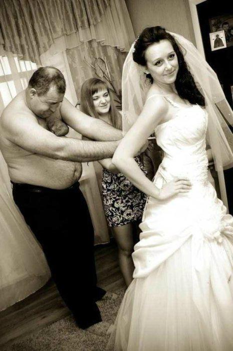Padre acomodando vestido de hija