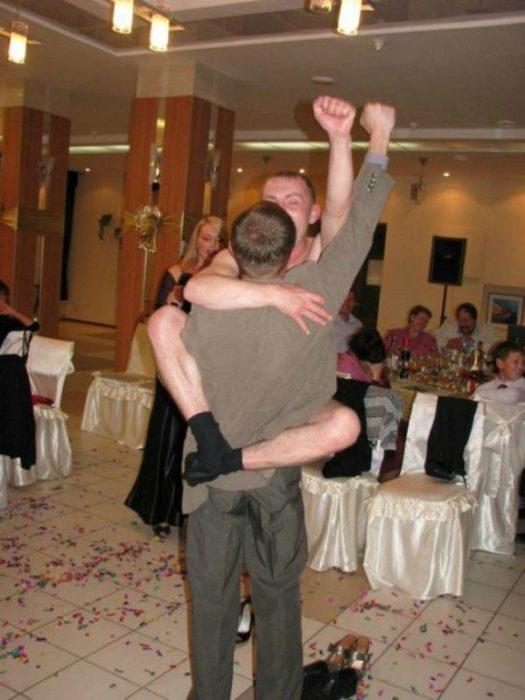 Hombre cargando a otro en señal de triunfo