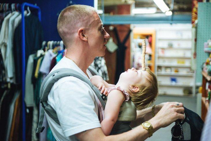 papá con una niña dormida y con cherrios en la zabeza