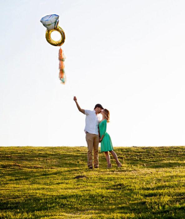 hombre tierno con un globo de anillo de compromiso