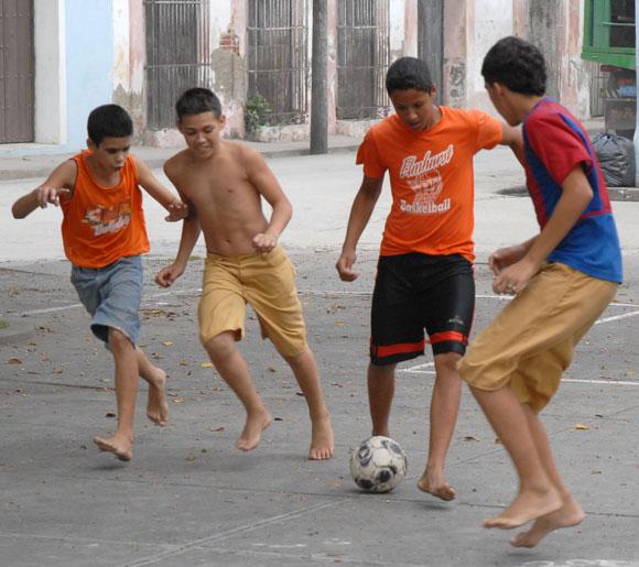 Niños jugando futbol en calle