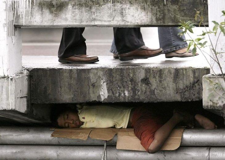 niño bajo la banqueta tratando dormir y pasando frio