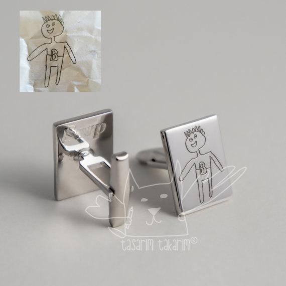 mancuernas de sus hijos en una placa de plata