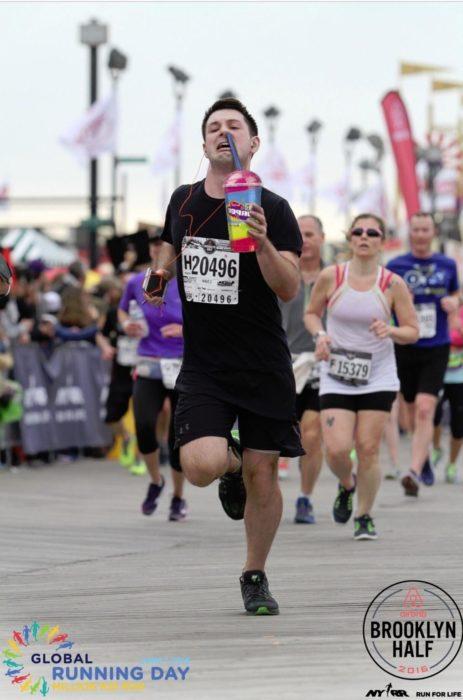 Maratonista tomando una bebida y el popote le sirve para tapar su nariz