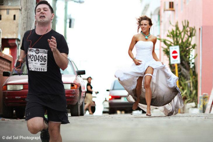 Maratonista con tapón en la nariz corriendo de una mujer vestida de novia