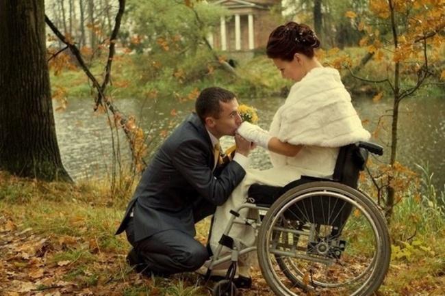 hombre besandole la mano a mujer en silla de ruedas