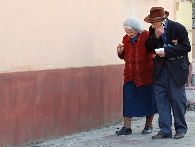 pareja de ancianos caminando y comiendo un helado