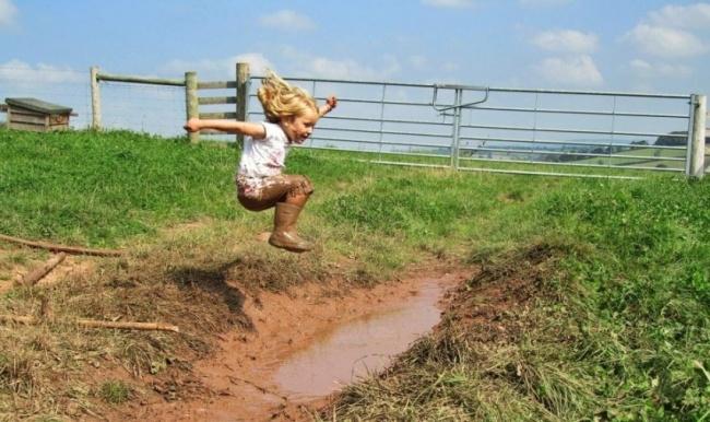 Niña saltando hacia charco de lodo