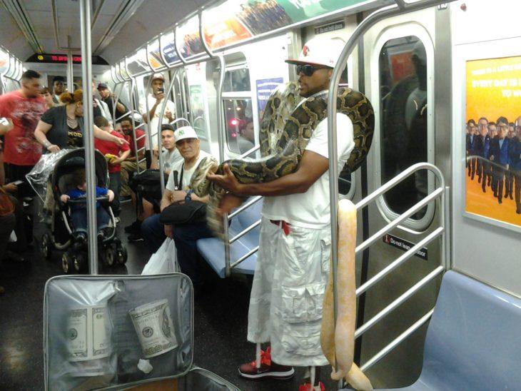 hombre viajando con unas serpientes en el metro