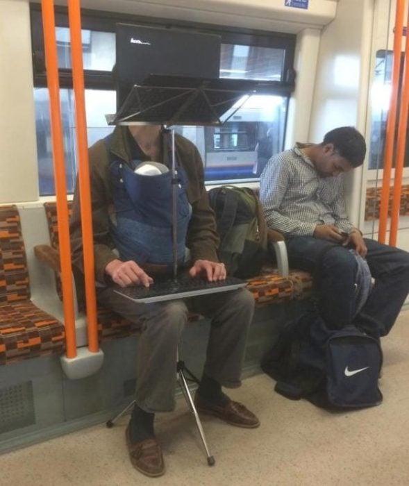 hombre con su computadora y un tripode en medio del metro con su bebpe en el cangurero que trae cargado