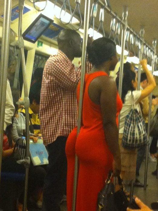 mujer con un tubo entre sus nalgas