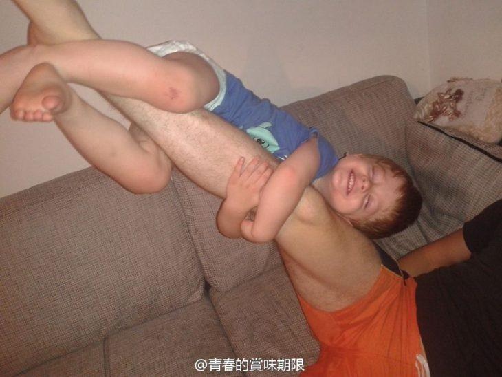 Niño en la pierna de su papá mientras él la levanta