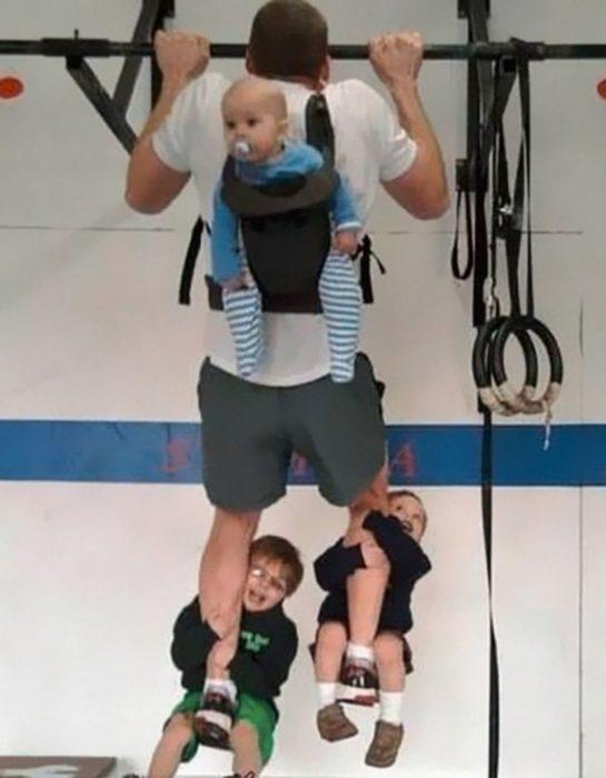 Papá ejercitándose con dos hijos en cada pierna y un bebé en la espalda