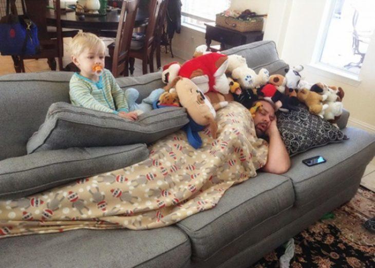 Papá dormido en el sillón entre los peluches