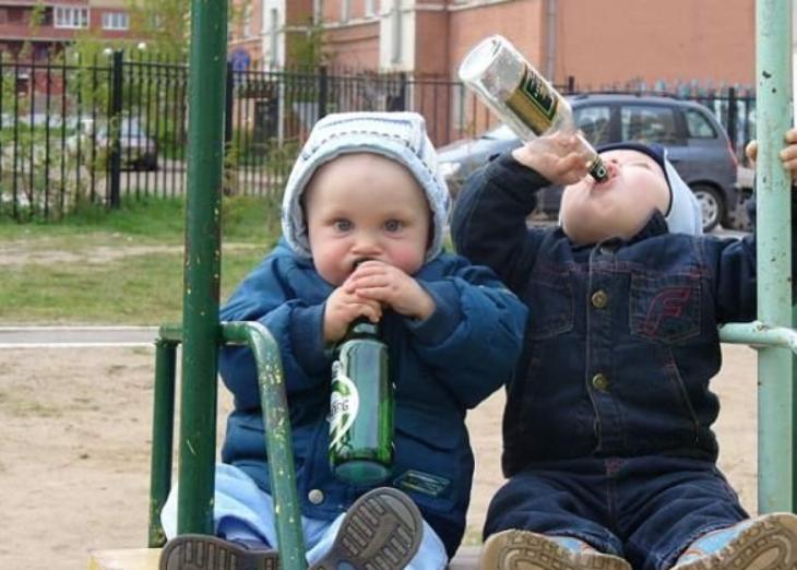 Niños pequeños tomando cerveza en columpio
