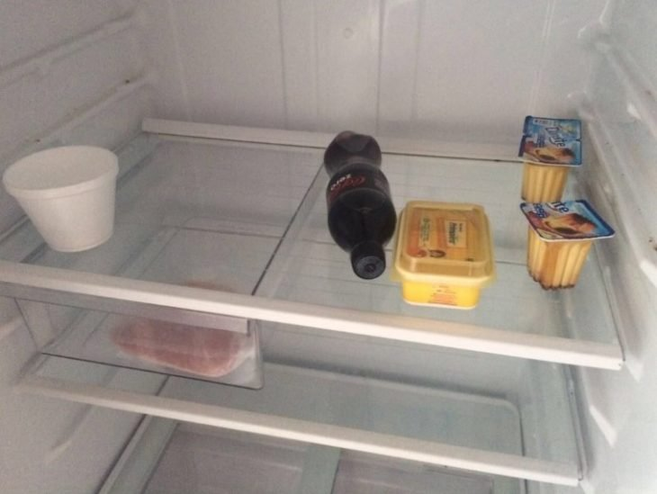 Situaciones estudihambre. Refrigerador con una botella de coca cola, 3 flanes, jamón, mantequilla y un envase