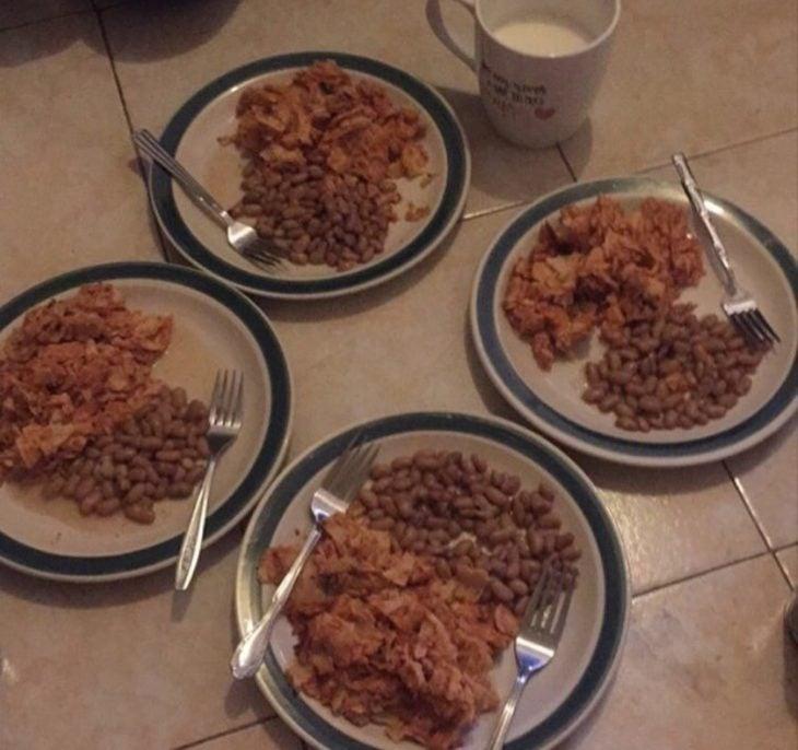 Situaciones estudihambre. 4 platos con frijoles y chilaquiles en el piso